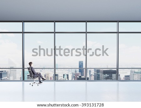 Businessman sitting on chair. Panoramic window with Paris view in front. Concept of thinking. - stock photo