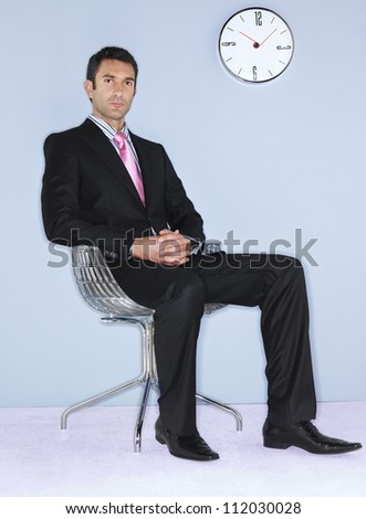 Businessman sitting on chair with wall clock in background
