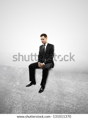 Businessman sitting on concrete wall