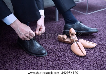 businessman sitting on couch and tying his shoelaces - stock photo