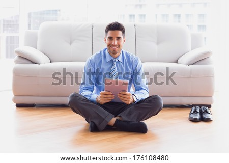Businessman sitting on floor using tablet pc smiling at camera in the office - stock photo