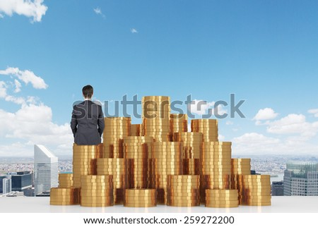 businessman sitting on gold coins on table and looking to city - stock photo