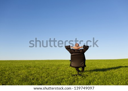Businessman sitting on green grassland under blue sky