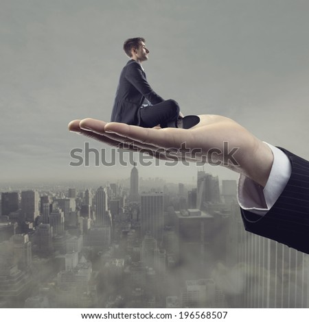 Businessman sitting on hand palm and looking away with cityscape and sky on background.