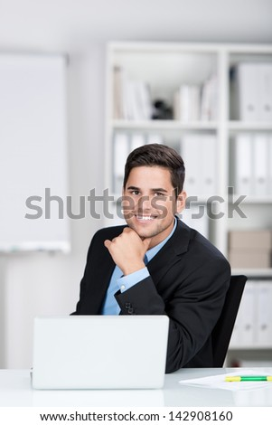 Businessman sitting on his desk and smiling for the camera. - stock photo
