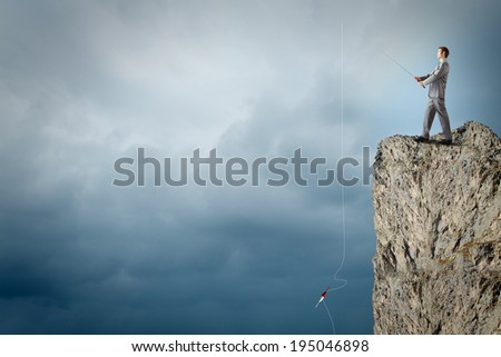 Businessman sitting on rock and fishing with rod
