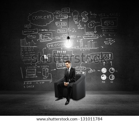 businessman sitting on sofa and global concept on wall - stock photo
