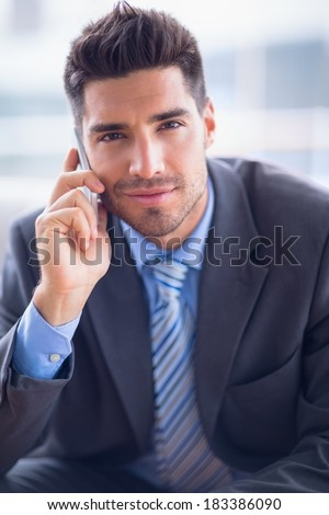 Businessman sitting on sofa making a call smiling at camera in the office - stock photo