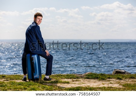 Businessman sitting on suitcase at seaside
