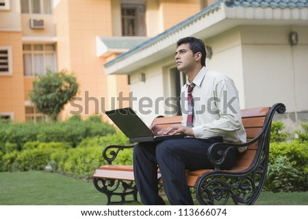 Businessman sitting on the bench and using a laptop - stock photo