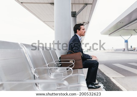 Businessman sitting on the chair at the airport bus stop and looking away, side view