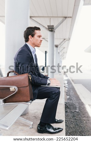 Businessman sitting on the chair at the bus station, side view - stock photo