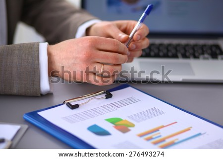Businessman sitting on the desk  - stock photo
