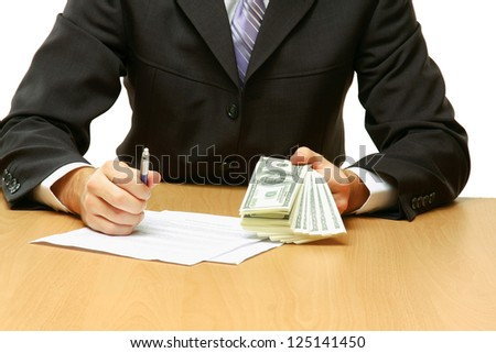 Businessman sitting on the desk and holding money in a hand - stock photo