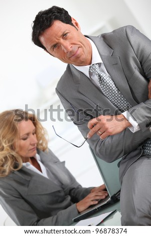 Businessman sitting on the desk of a colleague - stock photo
