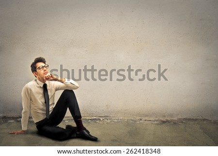 Businessman sitting on the ground  - stock photo