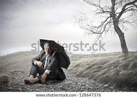 businessman sitting on the ground with umbrella