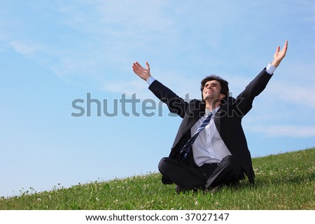 businessman sitting  on the meadow with hands up