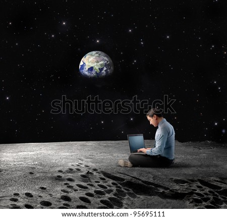 "Businessman sitting on the Moon and using a laptop with Earth in the background ""Elements of this image furnished by NASA"" - stock photo"