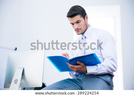 Businessman sitting on the table and reading document in office - stock photo