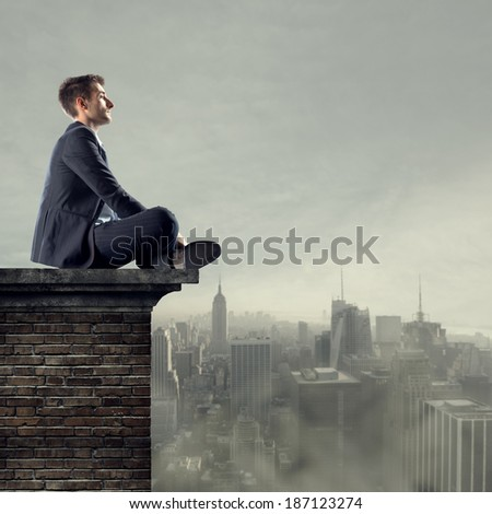 Businessman sitting on top of a building looking far away with cityscape on backgound.
