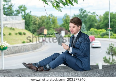 Businessman sitting outdoors and drinking coffee and looking at the customer's making a video call