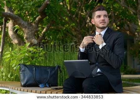 Businessman sitting outdoors and using computer