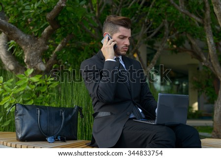 Businessman sitting outdoors and using computer while talking on phone