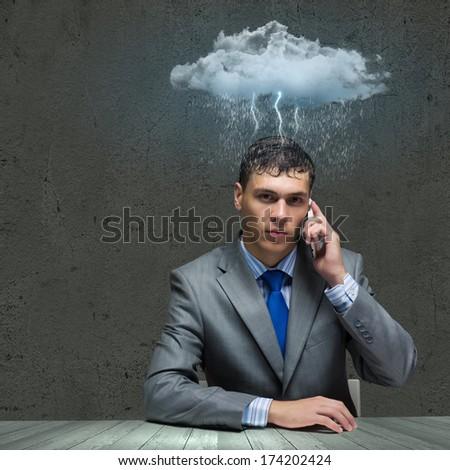 Businessman sitting under rain talking on mobile phone - stock photo