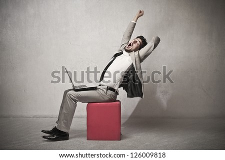 Businessman sitting with a laptop is stretching - stock photo