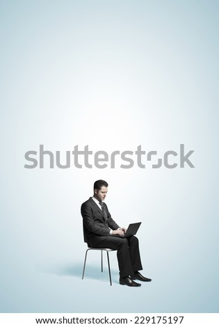 businessman sitting with laptop on blue background