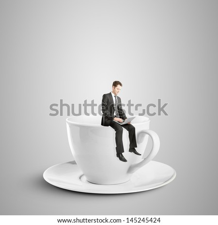 businessman sitting with laptop on cup - stock photo