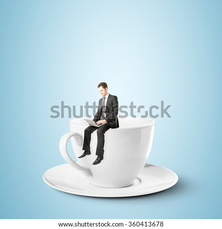 businessman sitting with notebook on big coffee cup - stock photo