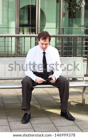 Businessman sitting with tablet outdoor