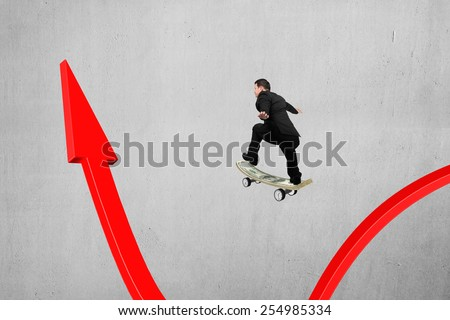 Businessman skateboarding on red arrow pointing up with concrete wall background - stock photo