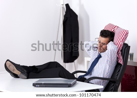 Businessman sleeping at his office with his shoes on the table