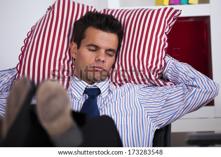 Businessman sleeping at his office with his shoes on the table - stock photo