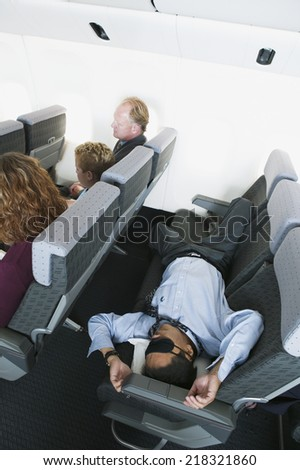 Businessman sleeping on airplane - stock photo