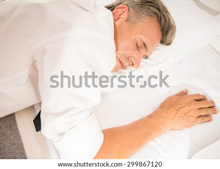Businessman sleeping on bed after hard working day at the hotel room. - stock photo