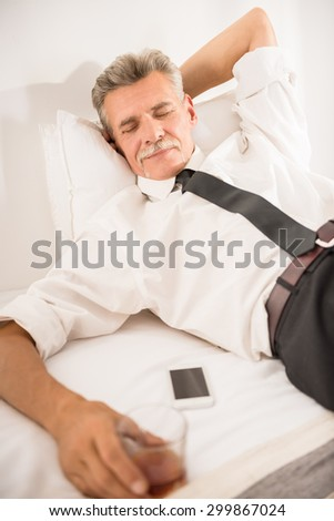 Businessman sleeping on bed after hard working day with glass of whiskey and his phone at the hotel room. - stock photo