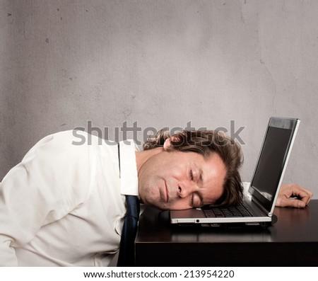 businessman sleeping on laptop on gray background - stock photo