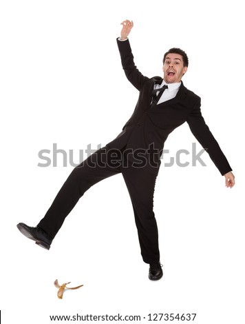 Businessman slipping on banana peel. Isolated on white