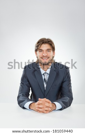 businessman smile at office desk, Handsome young business man sitting over gray background - stock photo
