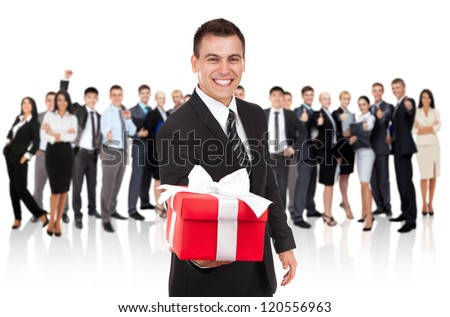 Businessman smile present gift red box in hand. With big group of Business people on background