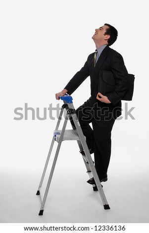 Businessman smiling as he climbs up a stepladder, briefcase in hand. Isolated against a white background - stock photo
