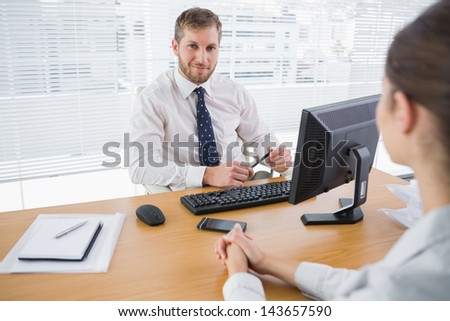 Businessman smiling at camera in his office with co worker at his desk - stock photo
