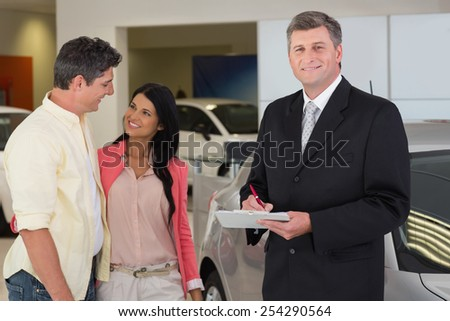 Businessman smiling at camera while writing on clipboard at new car showroom
