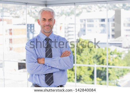 Businessman smiling at camera with arms crossed in his office - stock photo