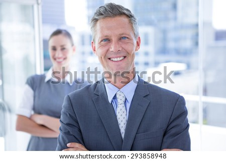 Businessman smiling at the camera while his colleague smiling in the background - stock photo
