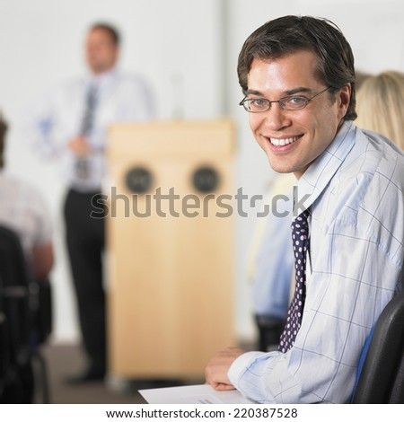 Businessman smiling in conference - stock photo